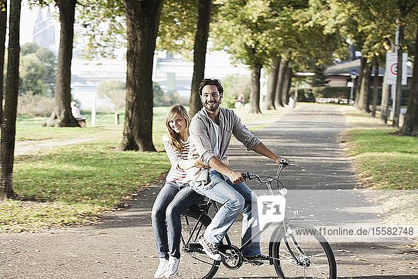 Deutschland  Köln  Junges Paar auf Fahrrad  lächelnd  Porträt