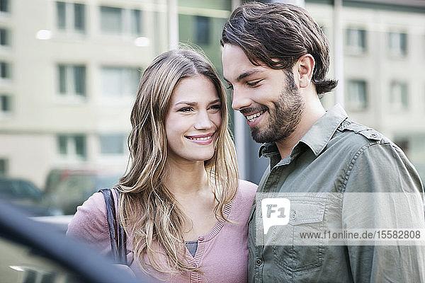 Deutschland  Köln  Junges Paar beim Auto  lächelnd