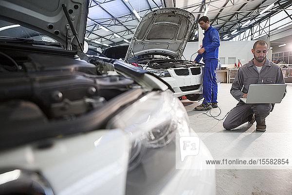 Zwei Automechaniker mit Laptop in Reparaturwerkstatt