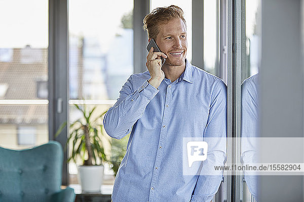 Smiling businessman on the phone at the window