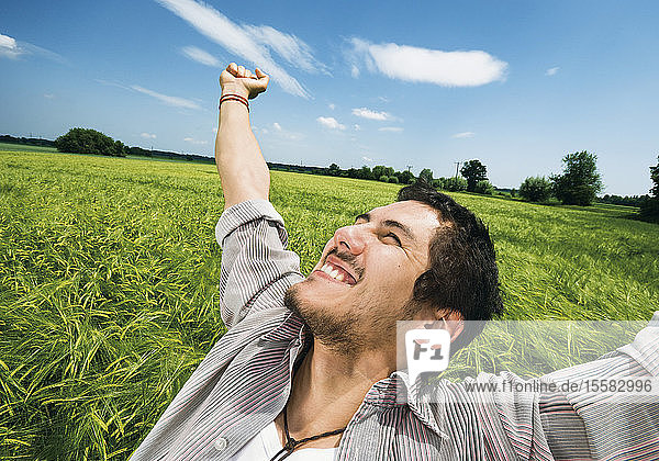 Germany  Young man with arms outstretched  smiling
