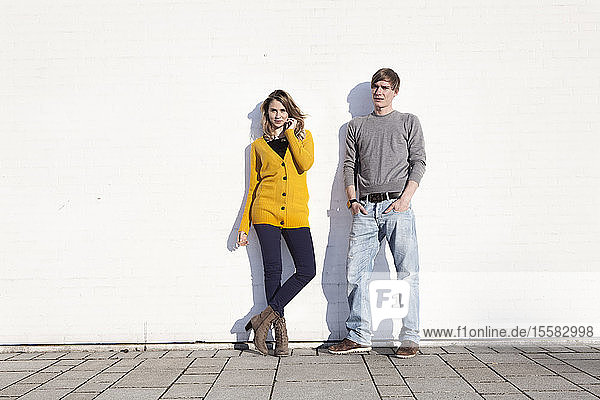 Germany  Bavaria  Munich  Young couple standing against wall