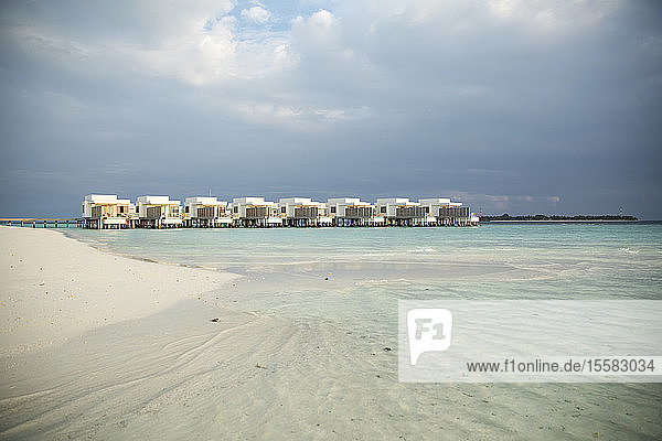 View of villas over sea against cloudy sky at Maldives