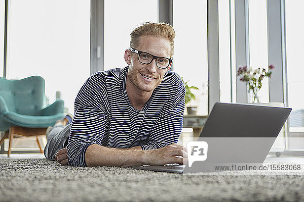 Portrait of smiling young man lying on carpet at home using laptop
