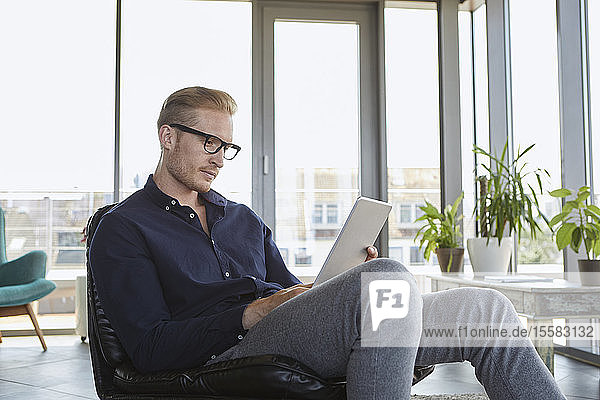Young man sitting in armchair at the window at home using tablet