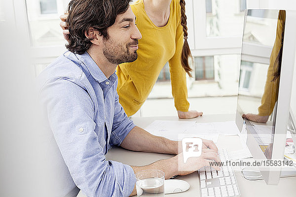 Couple in home office with man using computer