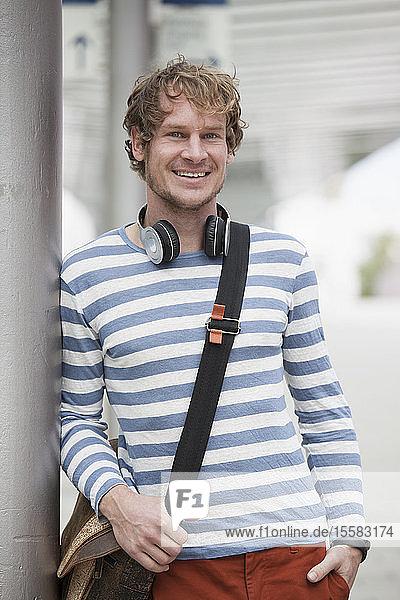 Portrait of smiling man with headphones and shoulder bag