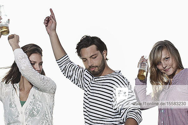 Deutschland  Köln  Junger Mann und Frau tanzen mit Bierflaschen und lächeln