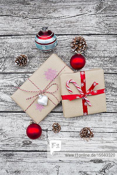 Eingepackte Weihnachtsgeschenke  Weihnachtskugeln und Tannenzapfen auf Holz