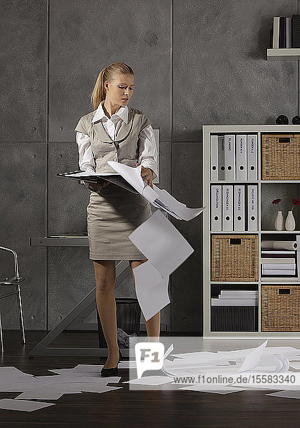 Junge Frau hält Akte mit auf dem Boden liegenden Papieren