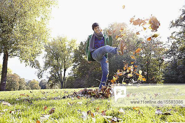 Deutschland  Köln  Junger Mann spielt mit Blättern im Park  lächelnd