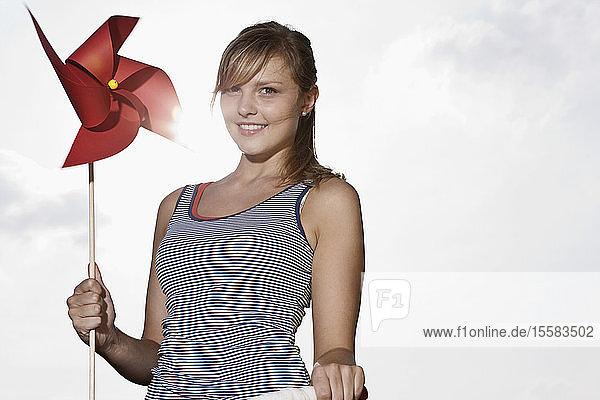 Deutschland  Köln  Junge Frau mit Windrad  lächelnd  Porträt