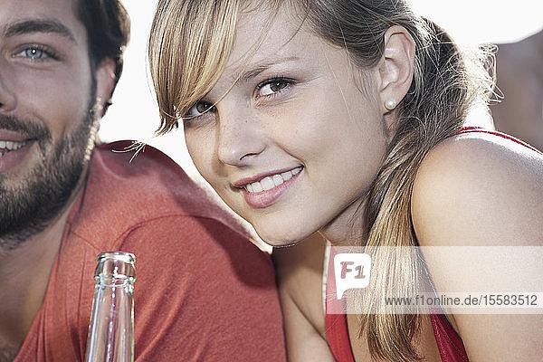 Deutschland  Köln  Junges Paar mit Bierflasche  lächelnd  Porträt