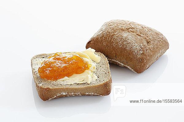 Brot mit Butter und Marmelade auf weißem Hintergrund