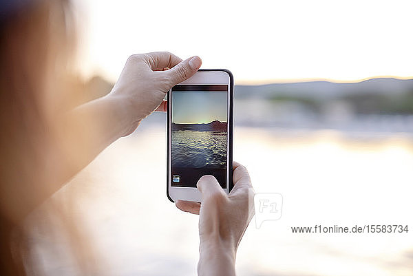 Close-up of woman taking cell phone picture of tbe sea at sunset