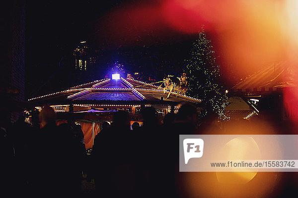 Deutschland  Silhouetten von Menschen auf dem beleuchteten Weihnachtsmarkt