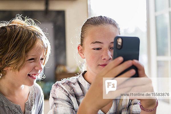 Ein Bruder und eine Schwester halten ein Smartphone hoch.