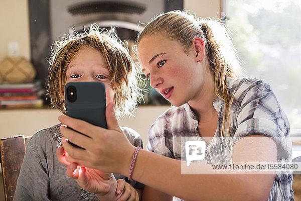 Zwei Kinder  ein Teenager und ihr sechsjähriger Bruder halten ein Smartphone in der Hand und nehmen sich selbst.