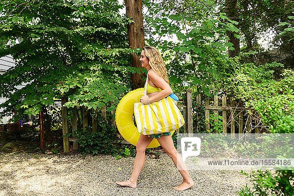 Junge Frau trägt gelbe Hüpfburg und Tasche