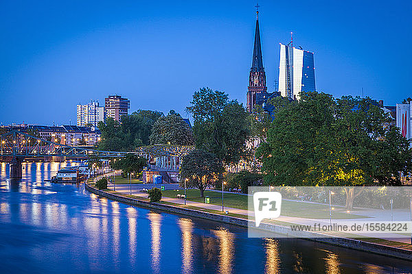 Church and office towers by river at sunset in Frankfurt  Germany