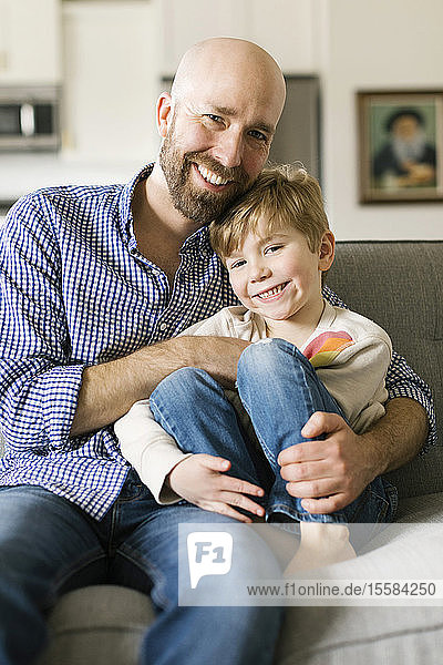 Father and son smiling on sofa
