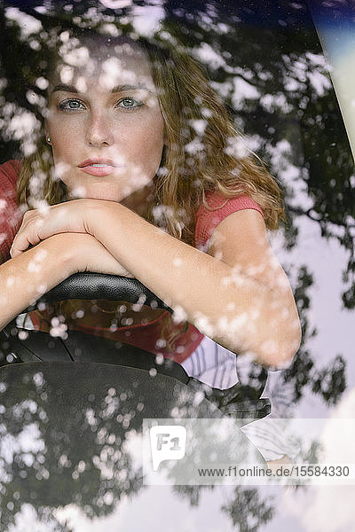 View through windscreen of young woman in car