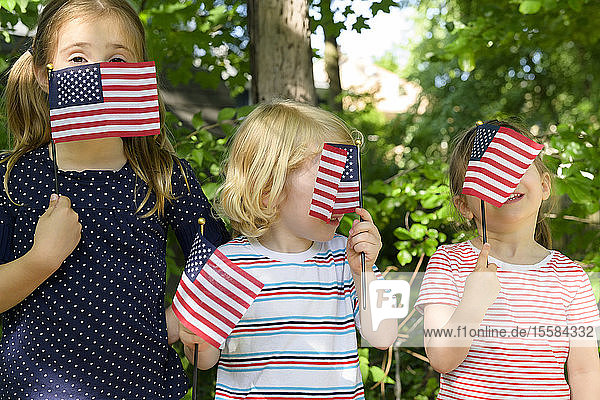 Children holding American flags over their faces