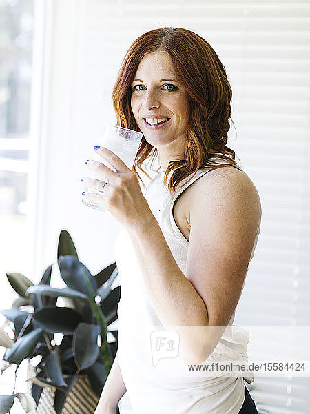 Mid adult woman holding glass of water