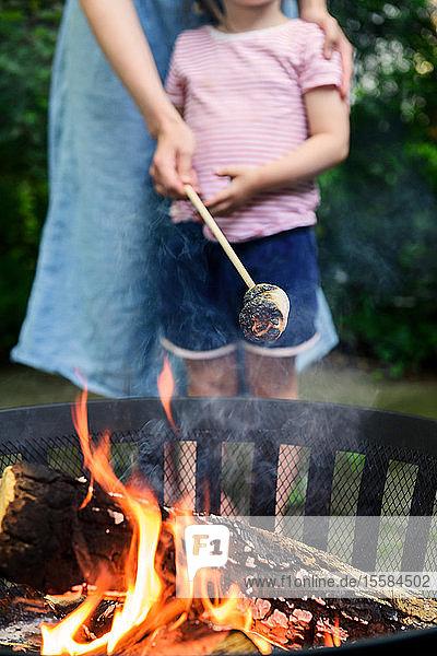 Mutter und Tochter rösten Marshmallows über einem Kohlenbecken