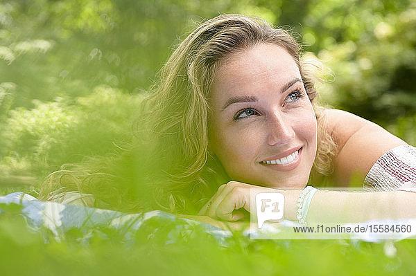 Lächelnde junge Frau im Garten liegend
