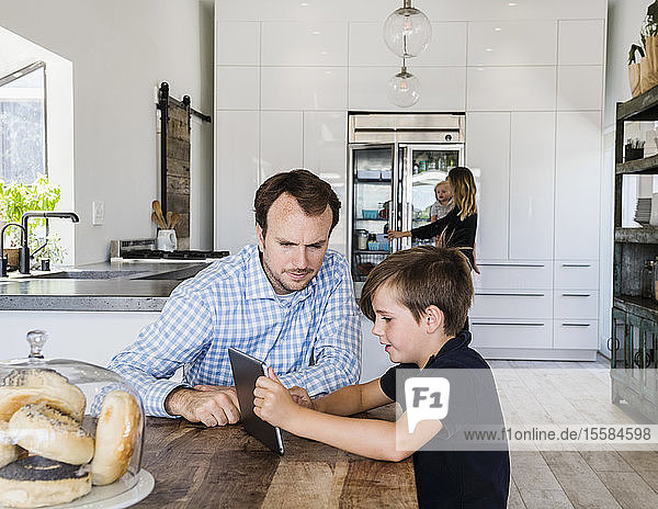 Father and son using digital tablet at dining table