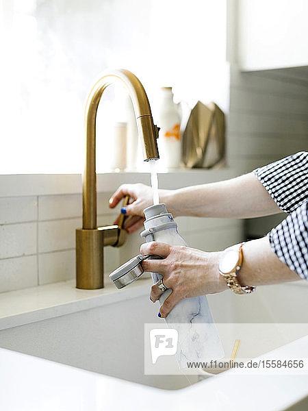 Hands of woman filling water bottle in kitchen sink