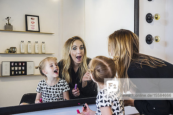 Mother and daughter applying lipstick in mirror