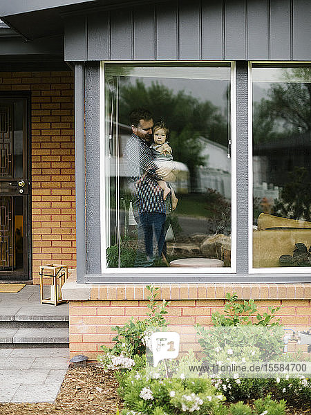 Father holding his daughter behind window of house