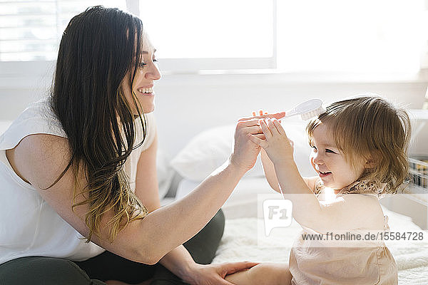 Mother and daughter on bed with hairbrush