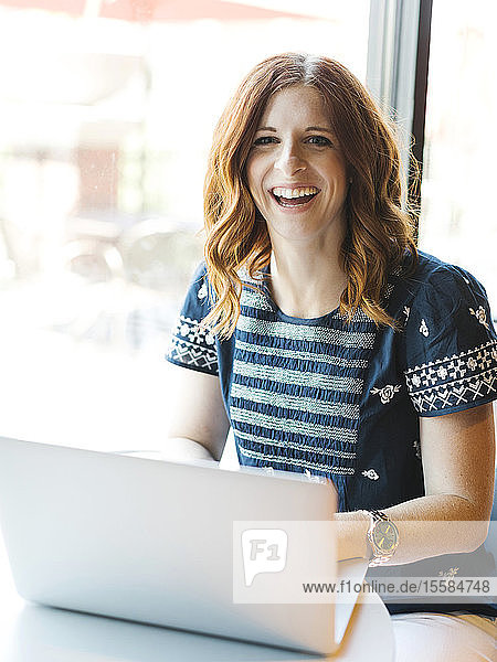 Smiling woman using laptop in cafe