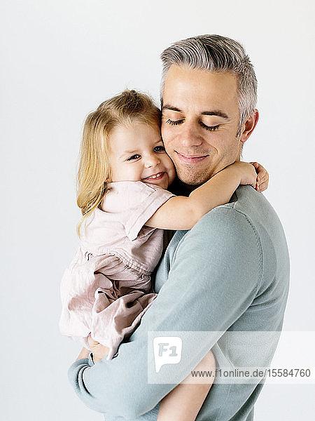 Smiling man holding his daughter