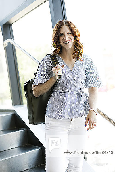 Smiling mid adult woman holding handbag on staircase