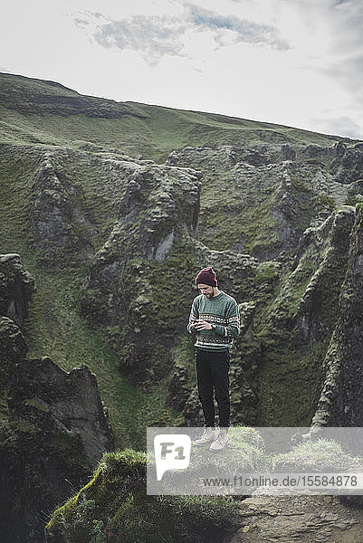 Man using smart phone on mountain in Kirkjubµjarklaustur  Iceland