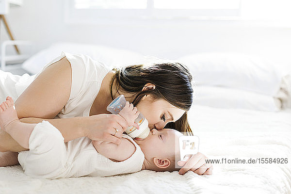 Mother kissing her son's cheek as he drinks bottle of milk