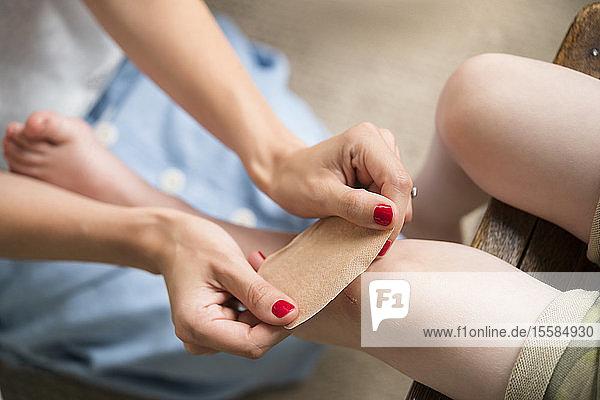 Mutter legt Verband um das Knie ihres Sohnes