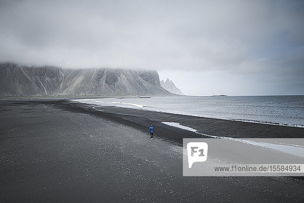 Man walking on black sand beach in Kirkjubµjarklaustur  Iceland