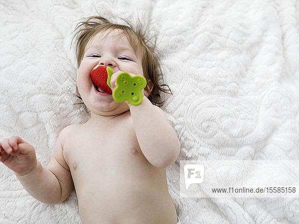 Baby girl lying on blanket biting strawberry toy