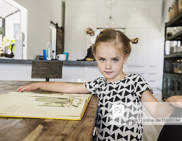 Girl at dining table with picture book