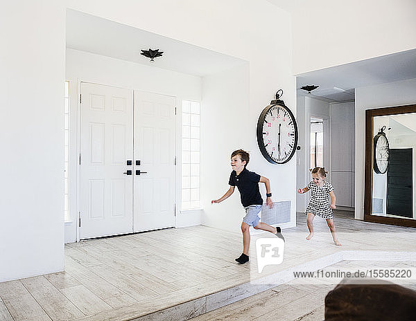 Girl chasing her brother in entrance hall