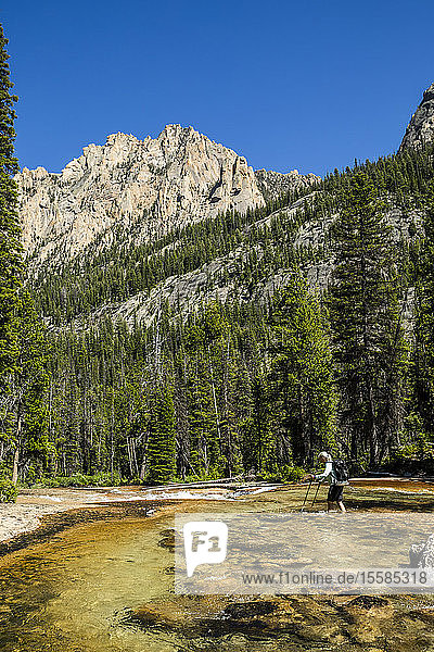 Woman wading through river by Sawtooth Mountains in Stanley  Idaho  USA