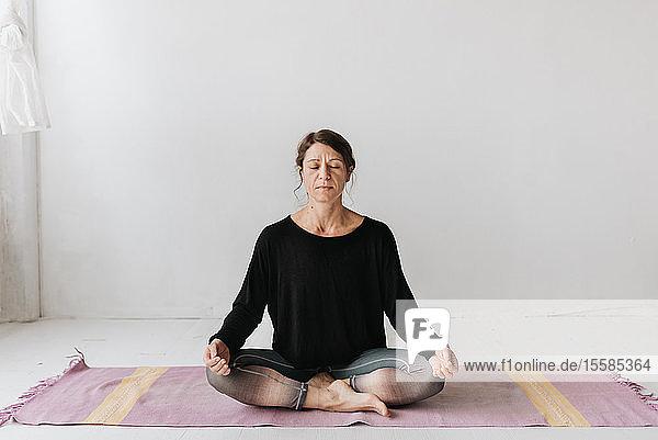 Frau sitzt in Lotus-Pose im Yoga-Studio