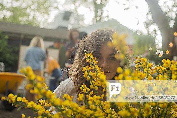 Junge Frau versteckt sich hinter gelber Blüte auf Gartenparty der Gemeinde  Kopf- und Schulterporträt