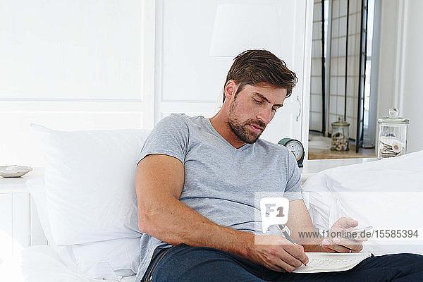 Mann benutzt Smartphone und schreibt Notizen auf dem Sofa
