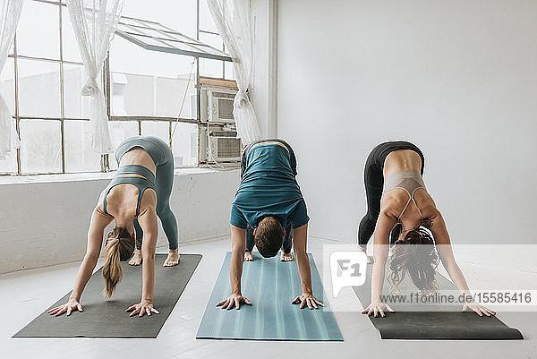 Friends practising yoga in studio